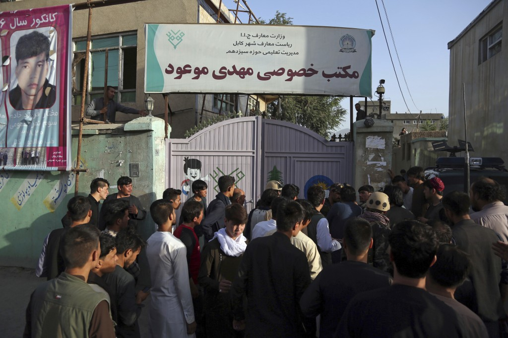 People gather at the site of a deadly suicide bombing that targeted a training class in a private building in the Shiite neighbourhood of Dasht-i Barc...