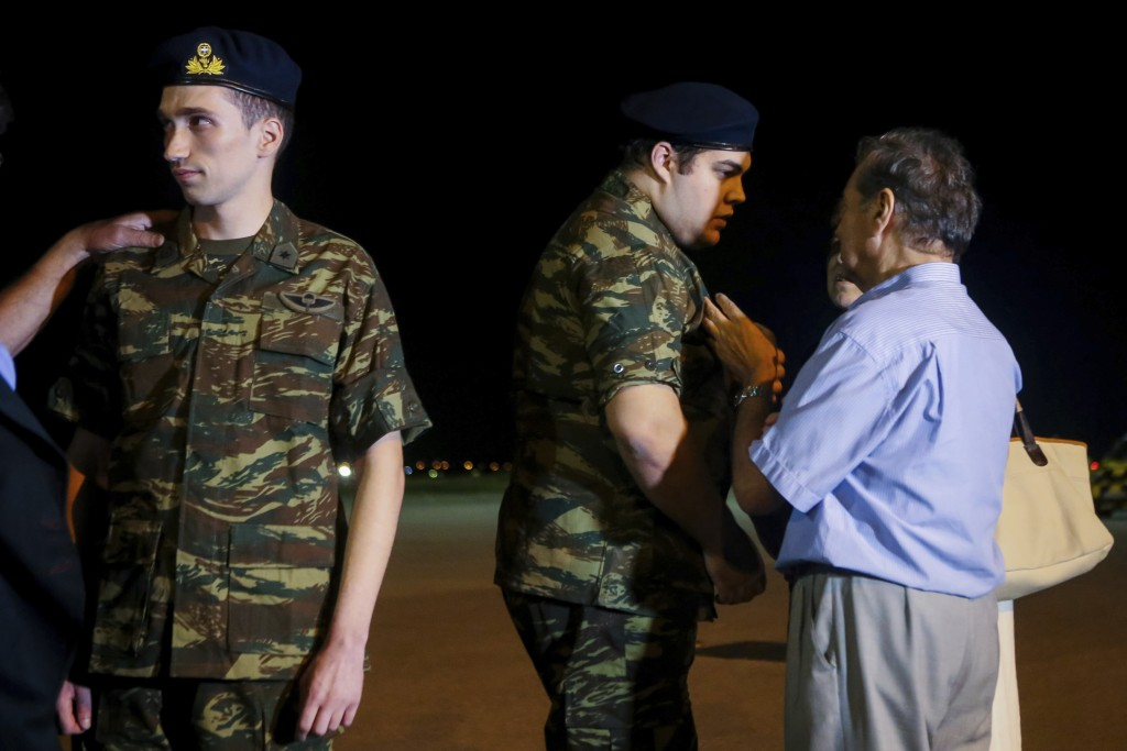 Greek soldiers Aggelos Mitretodis, left, and Dimitros Kouklatzis, second left chat with relatives after their arrival at the airport of the the northe...