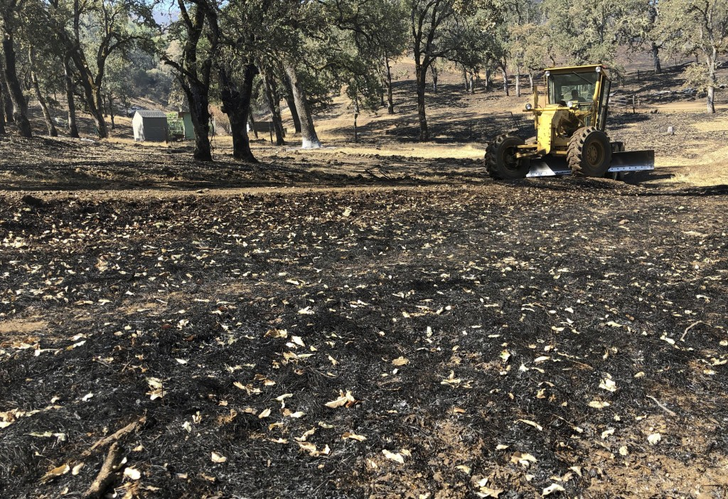 In this Friday, Aug. 10, 2018 photo, Jack Hattendorf steers a road grader to repair a dirt path near Lakeport, Calif. Even as flames continue chewing ...