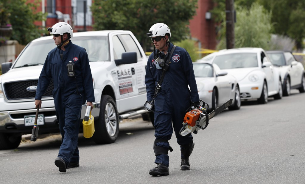 Search and rescue team members from the Denver Fire Department head to the scene of an apparent gas explosion in a row of homes Tuesday, Aug. 14, 2018...