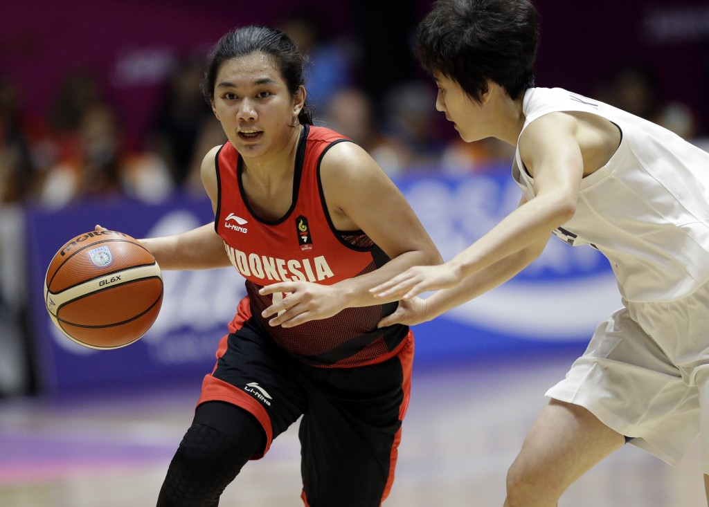Indonesia's Christine Tjundawan, left, dribbles the ball past combined Korea's Kim Hye Yon during their women's basketball match at the 18th Asian Gam...
