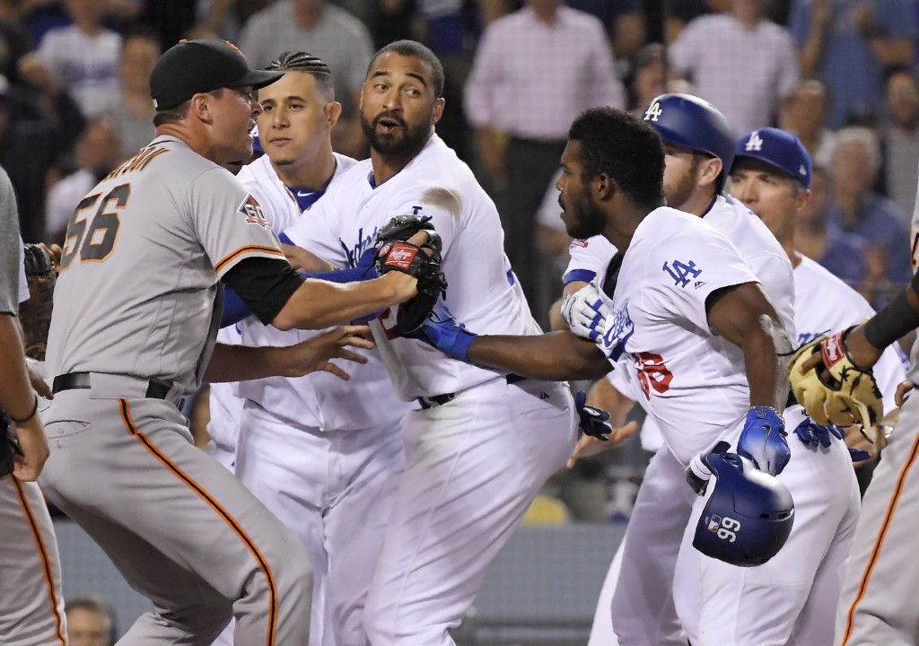 San Francisco Giants relief pitcher Tony Watson, left, scuffles with Los Angeles Dodgers' Yasiel Puig, right, as other members of the Dodgers get invo...