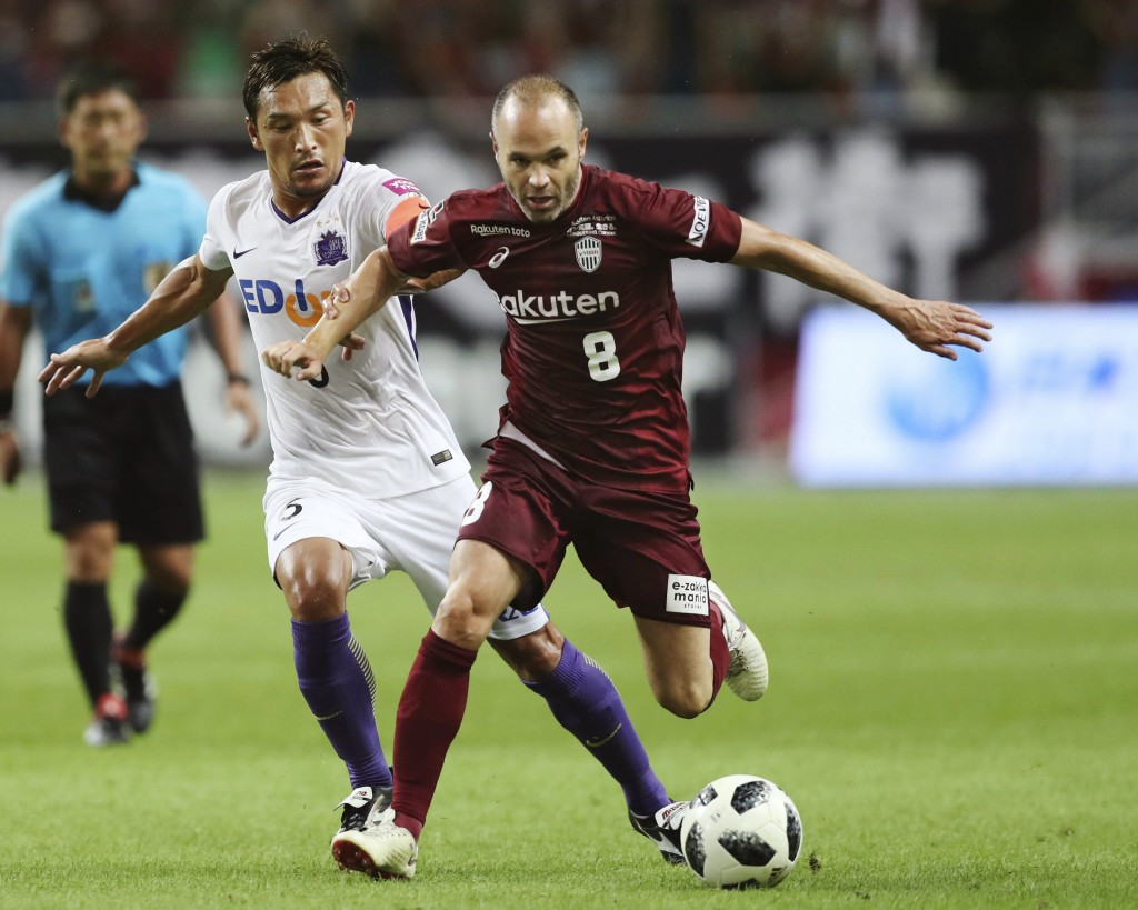Vissel Kobe's Andres Iniesta, right, fights for the ball with Sanfrecce Hiroshima's Toshihiro Aoyama during their J-League soccer match in Kobe, weste...