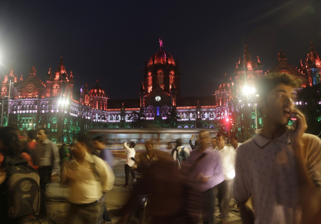 Commuters move past an illuminated Chhatrapati Shivaji Maharaj Terminus station building on the eve of Independence day in Mumbai, India, Tuesday, Aug...