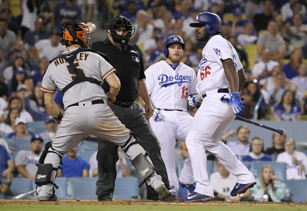 San Francisco Giants catcher Nick Hundley, left, reacts to being shoved by Los Angeles Dodgers' Yasiel Puig, right, as they argue while home plate ump...