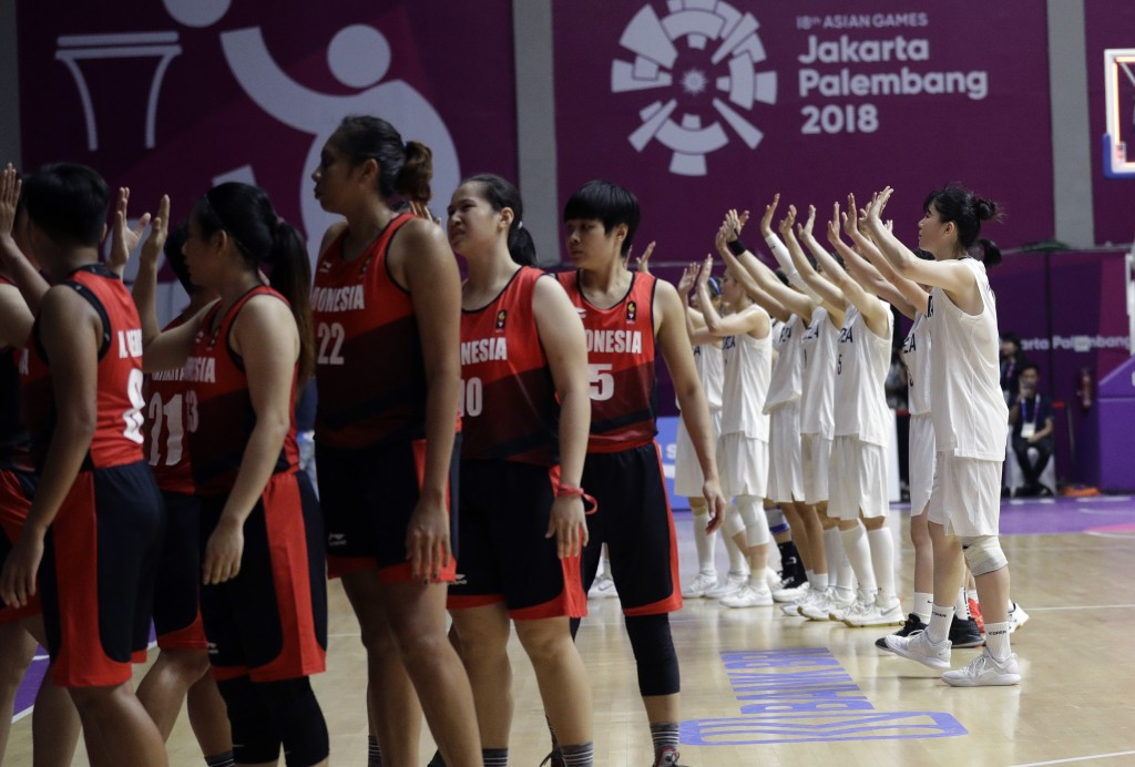 Combined Koreas players, right, wave to their supporters after defeating Indonesia in their women's basketball match at the 18th Asian Games in Jakart...