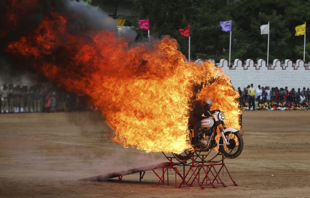 In this Wednesday, Aug. 15, 2018, photo, a member of ASC Tornados, the motorcycle display team of the Indian army, jumps through a fire ring as he per...