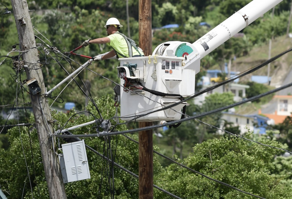 FILE- In this May 16, 2018 file photo, a worker from the Cobra Energy Company, contracted by the Army Corps of Engineers, installs power lines in the ...