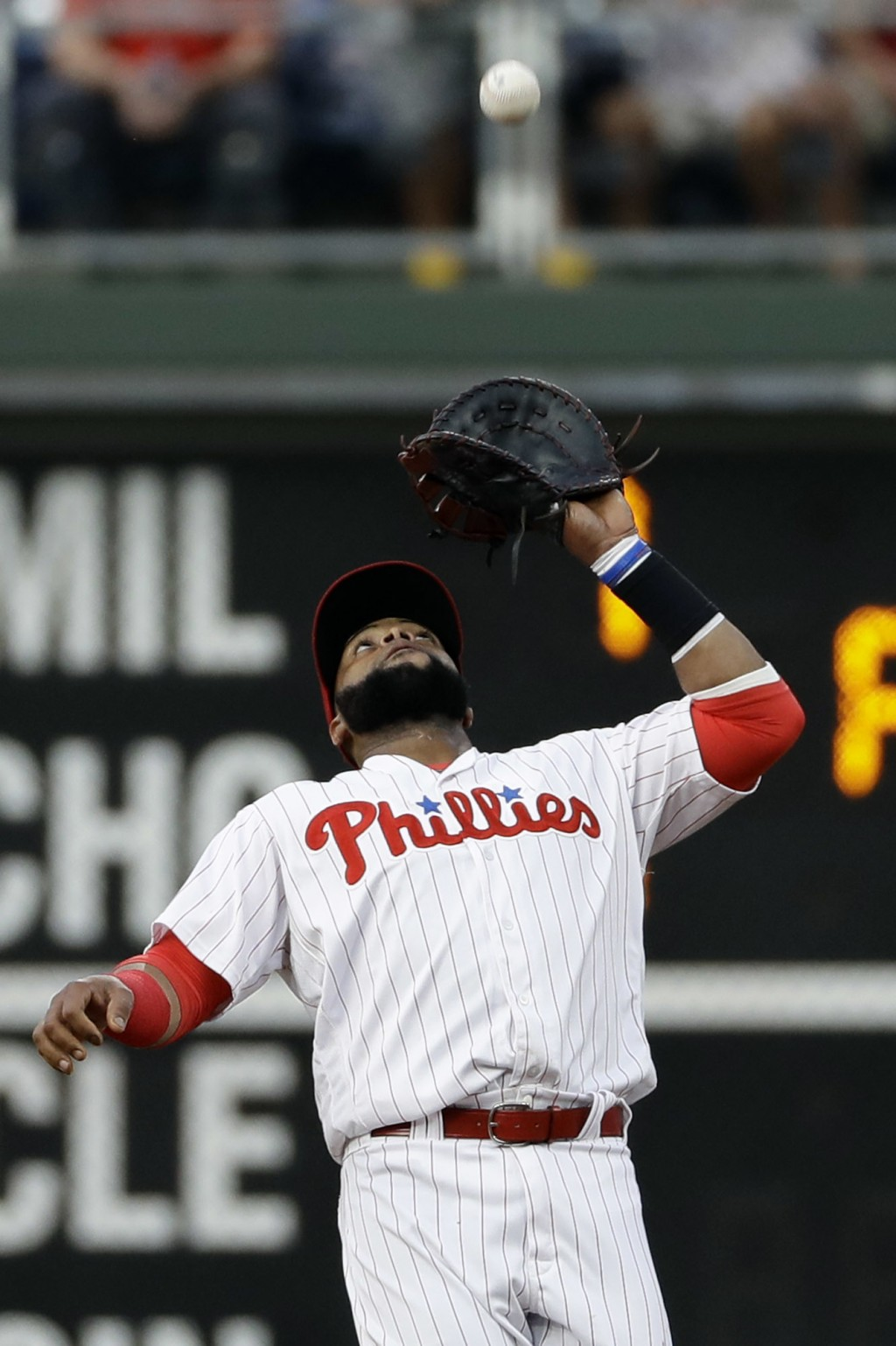 Philadelphia Phillies first baseman Carlos Santana catches a fly ball by Boston Red Sox's Mookie Betts during the first inning of a baseball game, Tue...