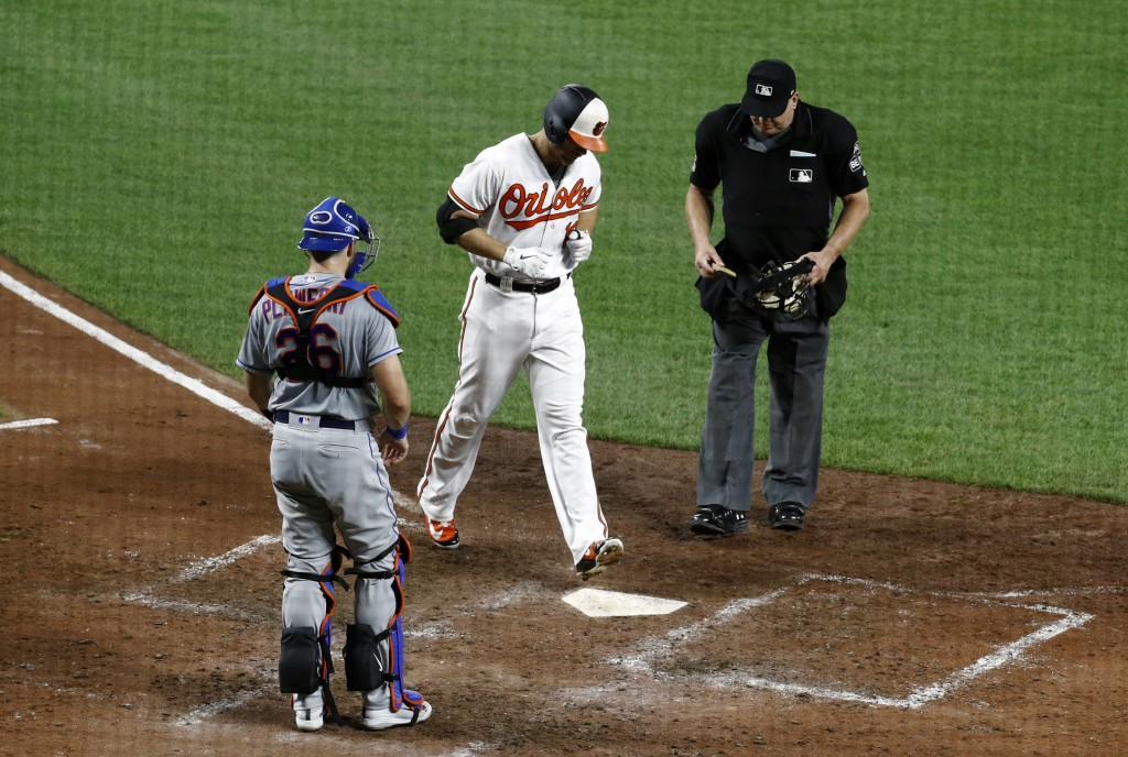 Baltimore Orioles' Chris Davis, center, crosses home plate in front of New York Mets catcher Kevin Plawecki, left, and umpire Jeff Nelson after roundi...