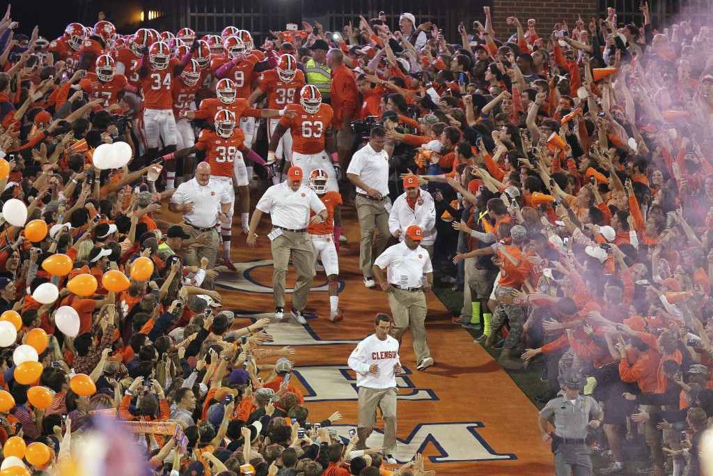FILE-This Oct. 19, 2013, file photo shoes Clemson head coach Dabo Swinney leading the team down the lane before the first half of an NCAA college foot...