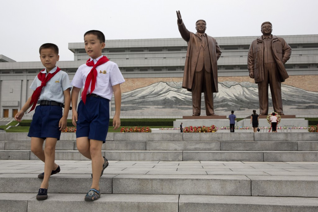 Children leave after paying their respects before the giant bronze statues of late North Korean leaders Kim Il Sung and his son Kim Jong Il during the...