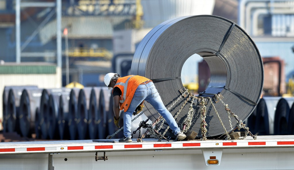 In this July 25, 2018, photo a truck driver chains down a roll of steel to his flatbed at the NUCOR Steel Gallatin plant in Ghent, Ky. The rolls, weig...