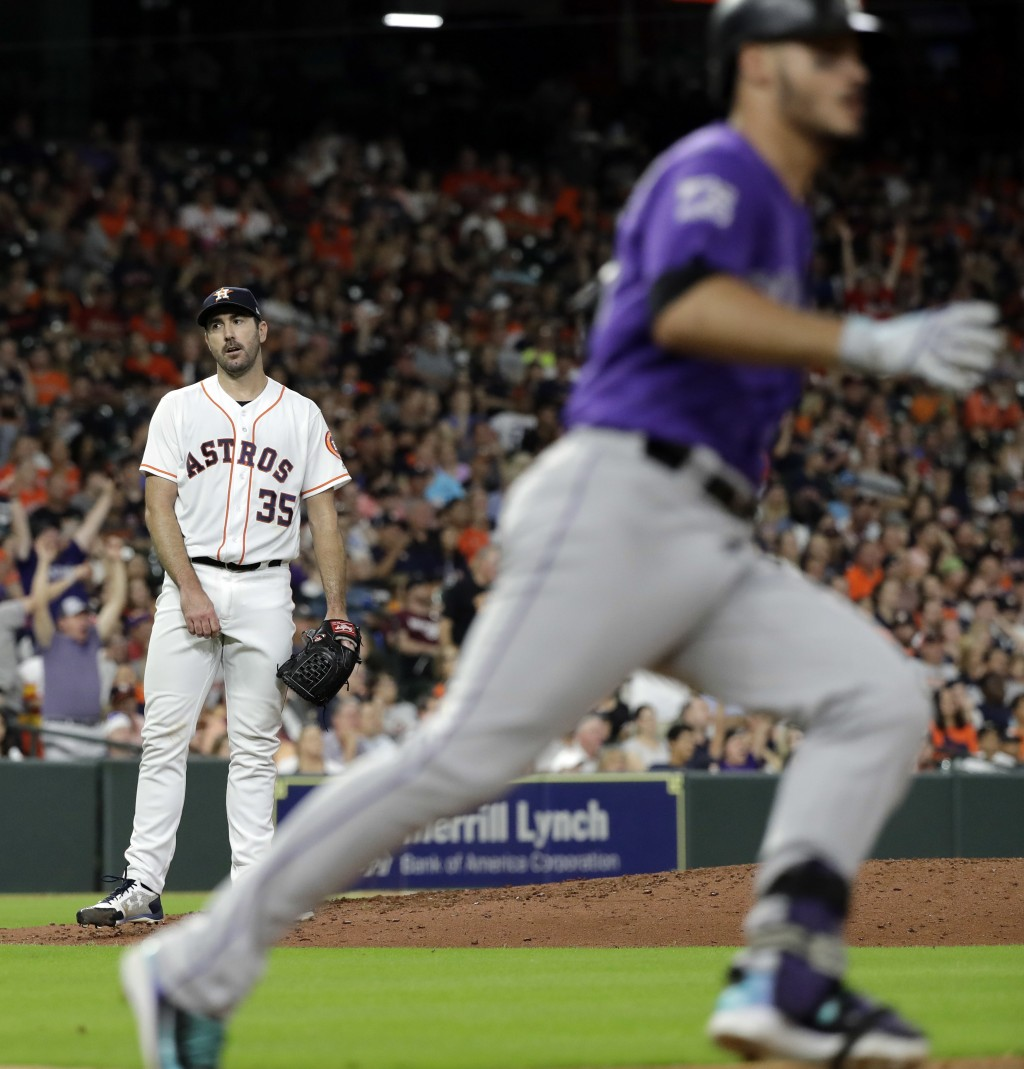Houston Astros starting pitcher Justin Verlander (35) reacts after Colorado Rockies' Nolan Arenado, right, hit a two-run home run during the sixth inn...
