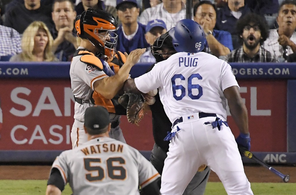 Los Angeles Dodgers' Yasiel Puig, right, shoves San Francisco Giants catcher Nick Hundley, left, as they argue while relief pitcher Tony Watson, below...
