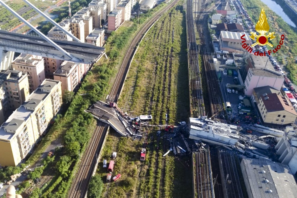 In this photo released by the Italian firefighters, rescue teams work among the rubble of the collapsed Morando highway bridge in Genoa, northern Ital...