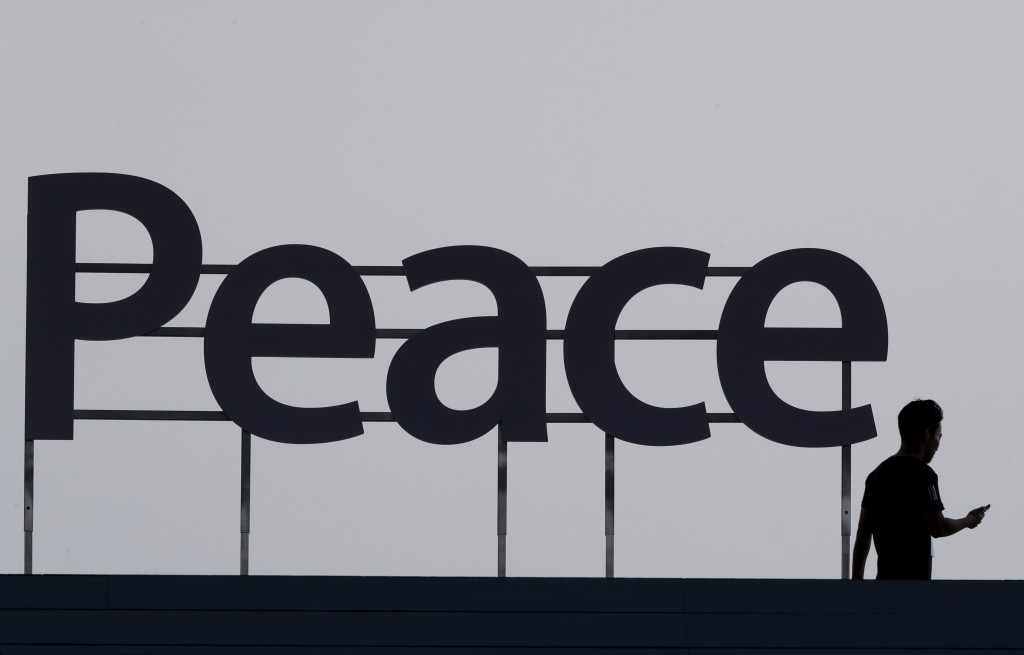 "In this Wednesday, Aug. 15, 2018, photo, a man walks by a ""Peace"" sign before a ceremony to celebrate Korean Liberation Day in Seoul, South Korea. (AP..."
