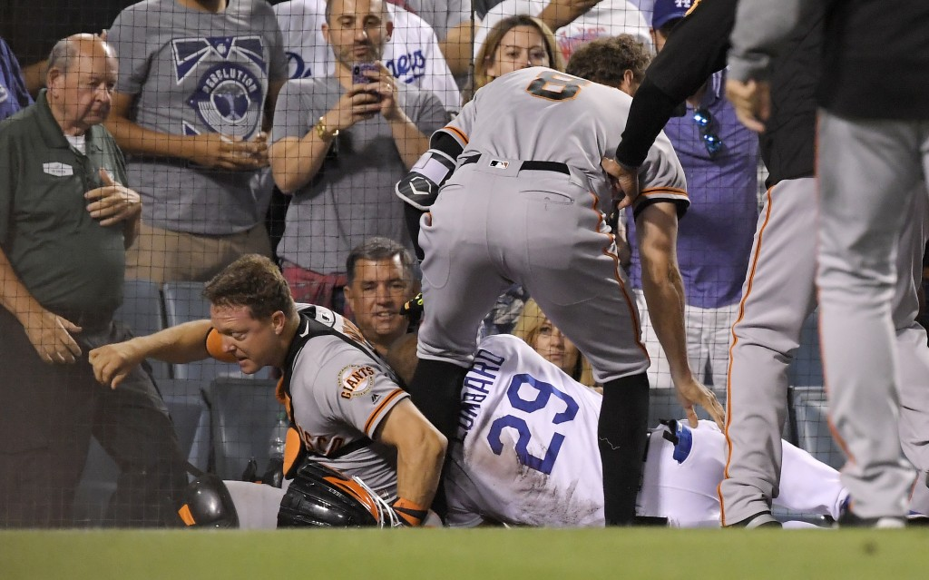 San Francisco Giants catcher Nick Hundley, left, and first base coach George Lombard, right, fall to the ground while Hunter Pence stands over them af...