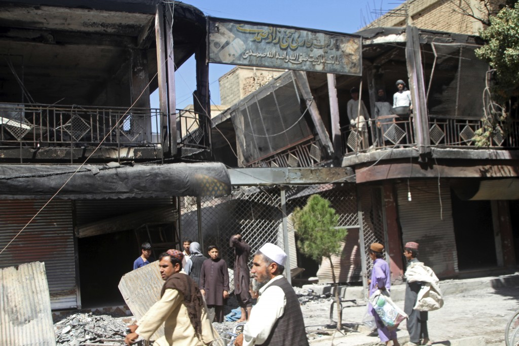 Afghan men stand in front of burned out shops following a Taliban attack in Ghazni, Afghanistan, Wednesday, Aug. 15, 2018. A Taliban assault on two ad...