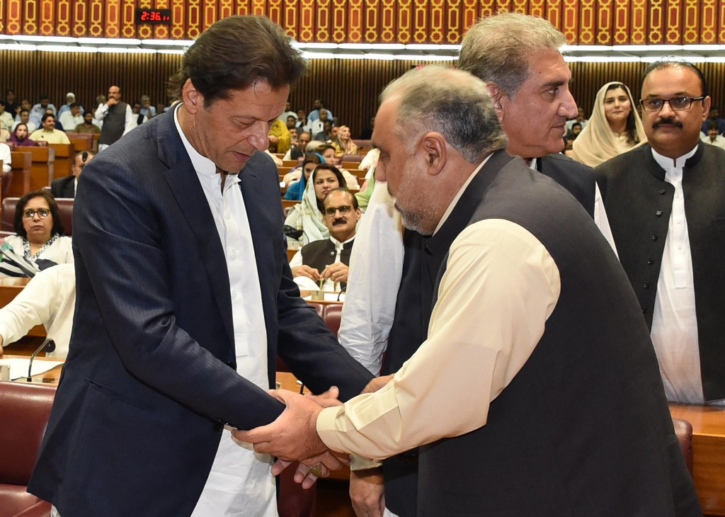In this photo released by the National Assembly, the leader of Pakistan Tahreek-e-Insaf party Imran Khan, left, greets speaker of the National Assembl...