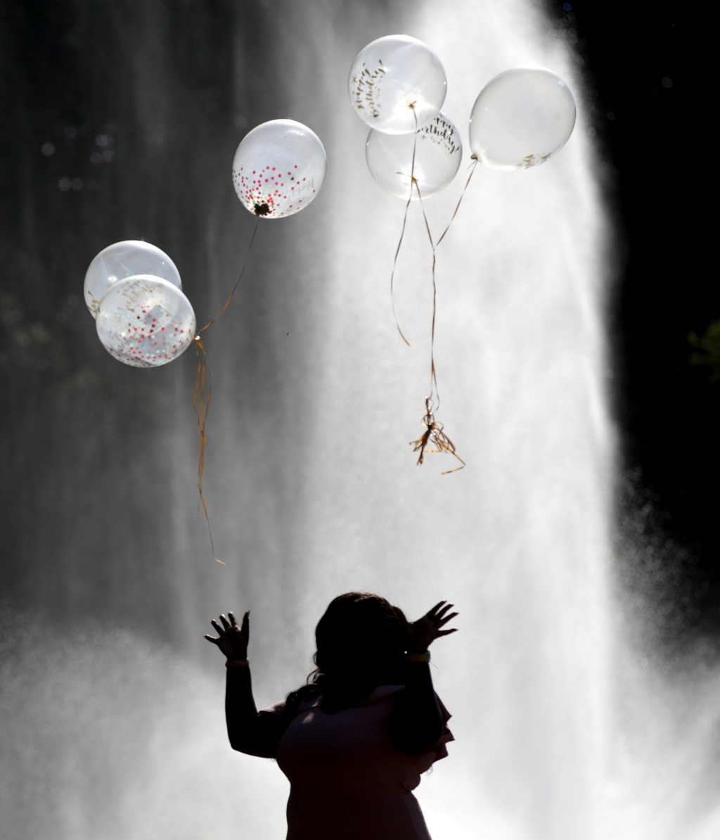 FILE- In this Oct. 5, 2017, file photo Annette Antwi, of Newark, N.J., releases balloons while celebrating her birthday in front of a fountain at Bran...