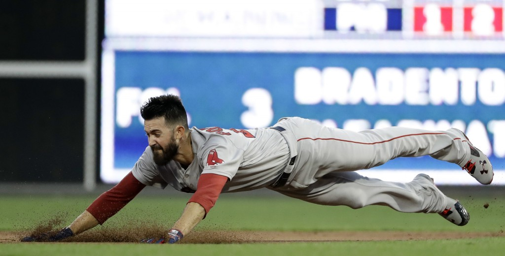 Boston Red Sox starting pitcher Rick Porcello dives into second base after hitting a double off Philadelphia Phillies starting pitcher Nick Pivetta du...