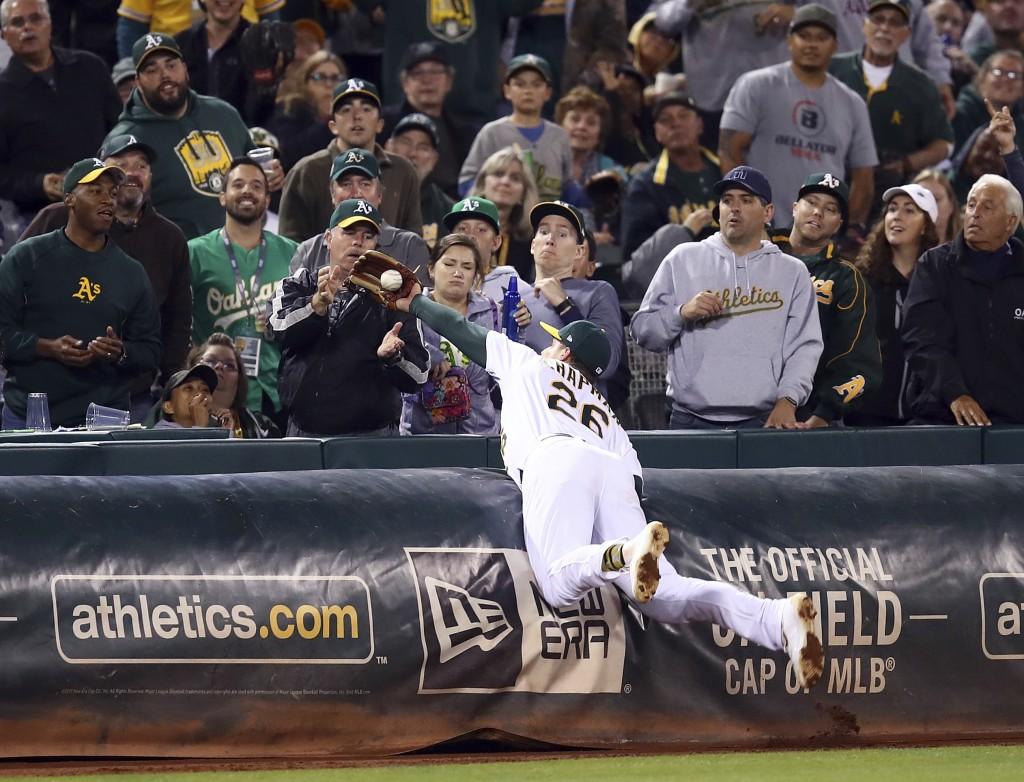 Oakland Athletics' Matt Chapman makes the catch on a foul ball hit by Seattle Mariners' Robinson Cano in the eighth inning of a baseball game, Tuesday...