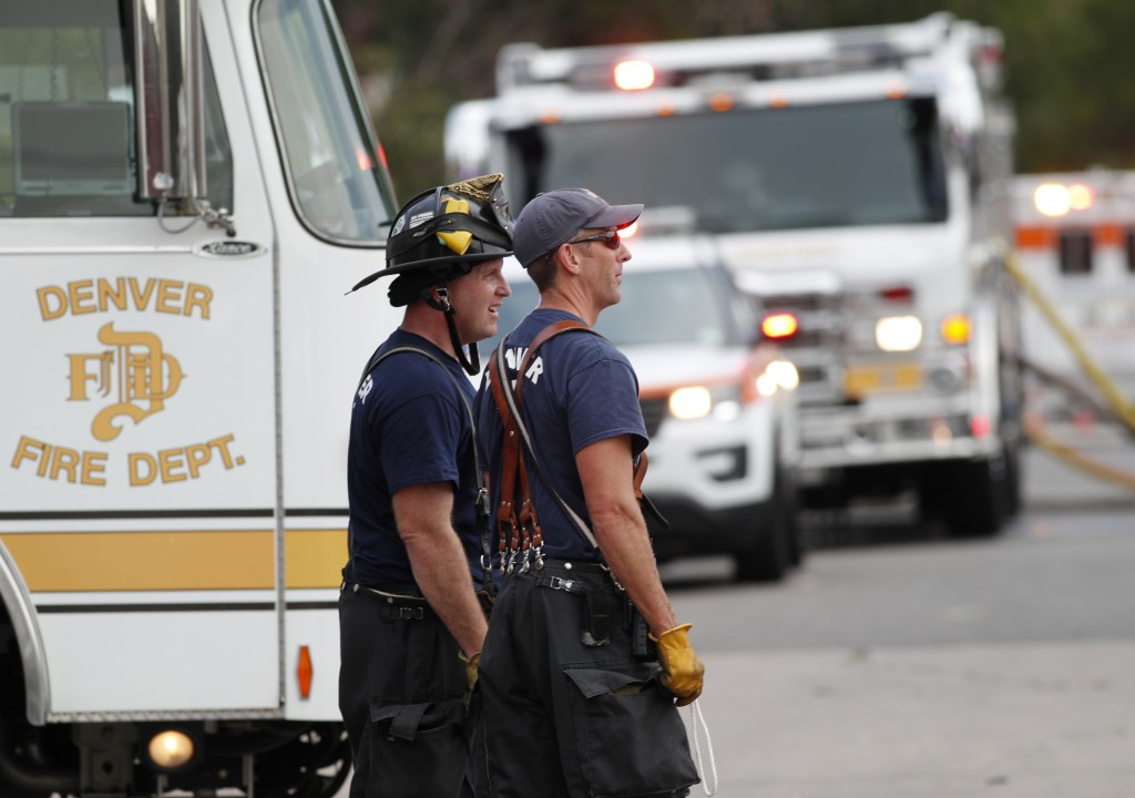 Denver Fire Department firefighters keep watch on the rubble from an apparent natural gas explosion in a row of homes strewn along a block Tuesday, Au...