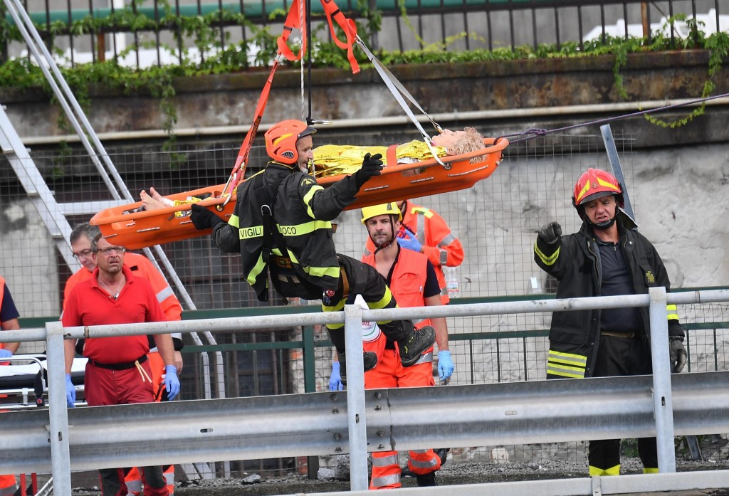 Rescuers recover an injured person after the Morandi highway bridge collapsed in Genoa, northern Italy, Tuesday, Aug. 14, 2018. A large section of the...