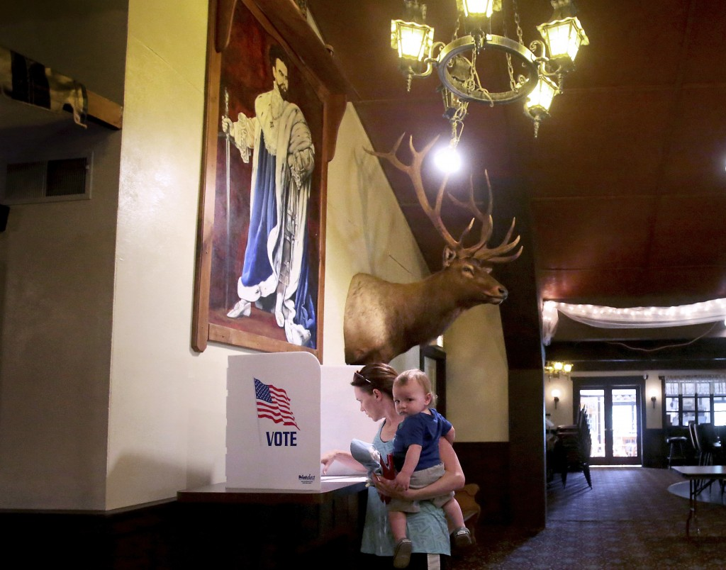 Marci Glaus holds her one-year-old son, Fredrick as she casts her vote during Wisconsin's primary election Tuesday, Aug. 14, 2018 in Roxbury, Wis.Demo...