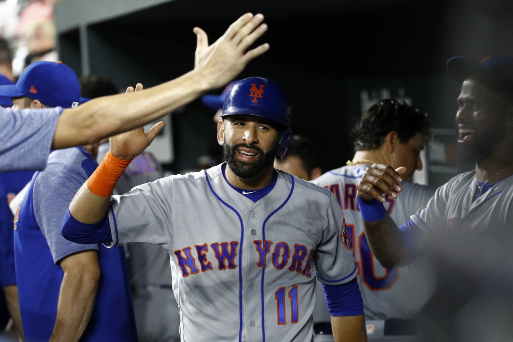 New York Mets' Jose Bautista (11) high-fives teammates in the dugout after scoring on Amed Rosario's single in the fifth inning of a baseball game aga...