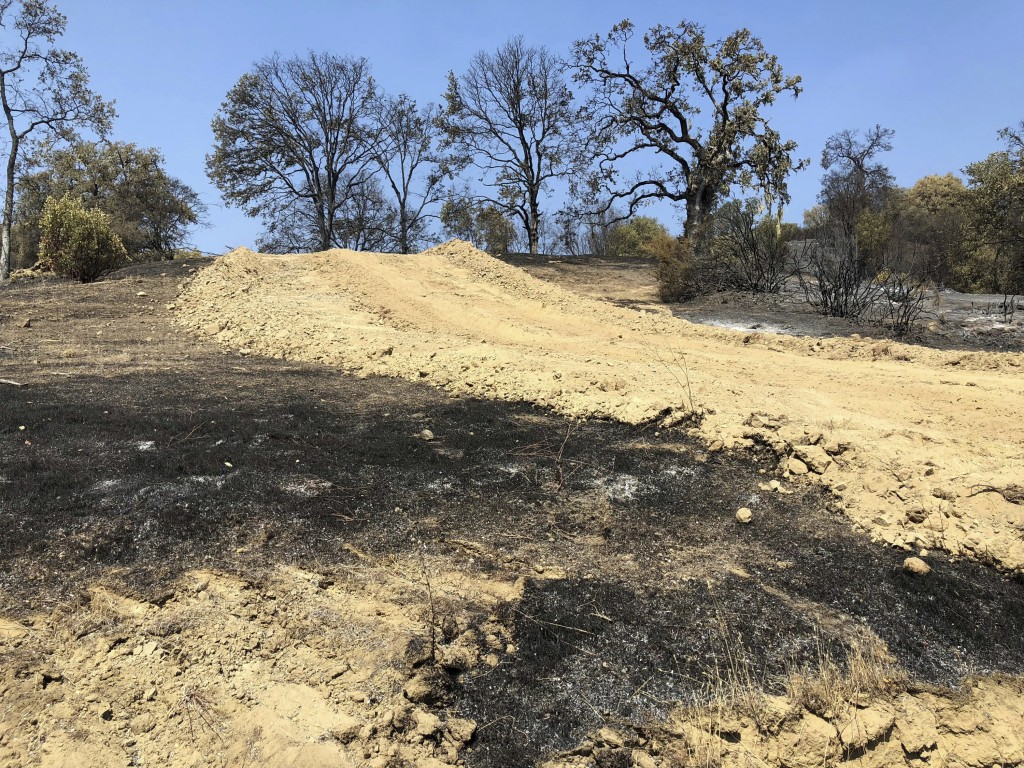 This photo taken Friday, Aug. 10, 2018 near Lakeport, Calif. shows a dirt path and dusty berms left behind when a bulldozer passed through private lan...