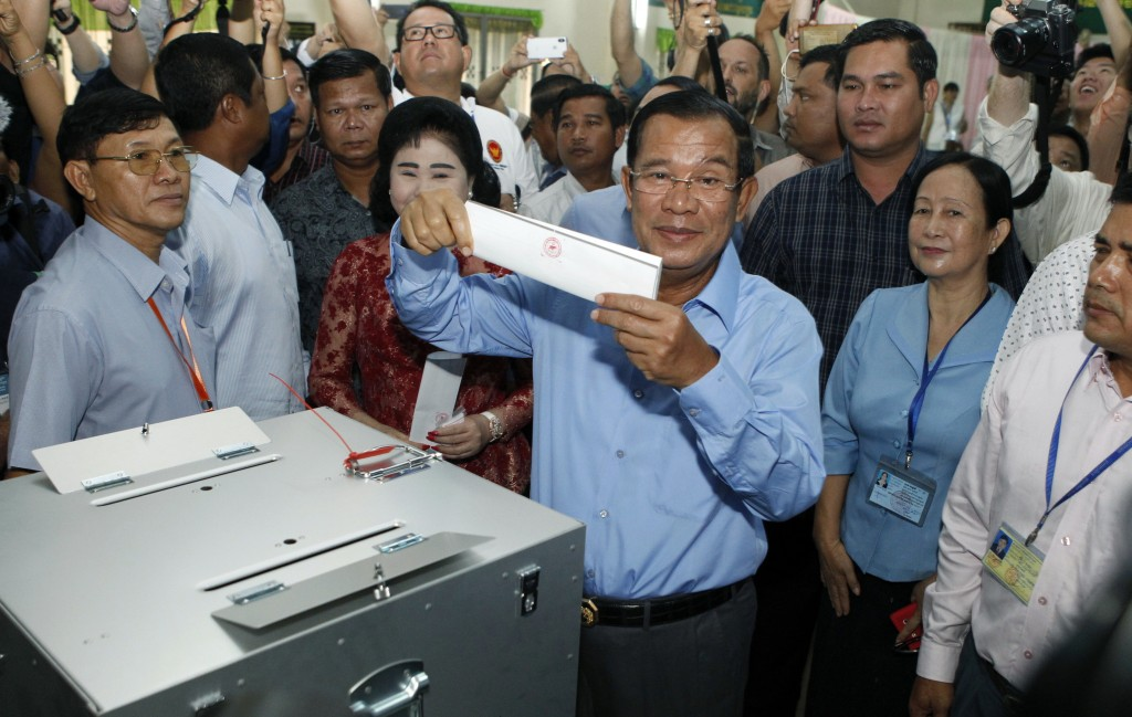 FILE - In this July 29, 2018, file photo, Cambodian Prime Minister Hun Sen, center, of the Cambodian People's Party (CPP), holds a ballot before votin...