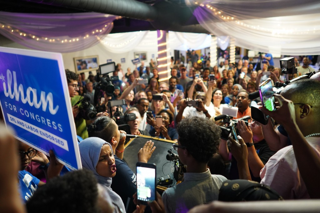 Minnesota Rep. Ilhan Omar, lower left wearing headdress, celebrates with her supporters after her Congressional 5th District primary victory, Tuesday,...