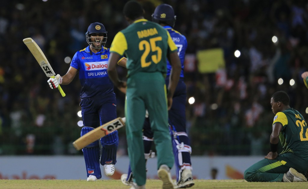 Sri Lanka's Dinesh Chandimal, left, and Isuru Udana celebrate their team's victory over South Africa by three wickets in their Twenty20 cricket match ...