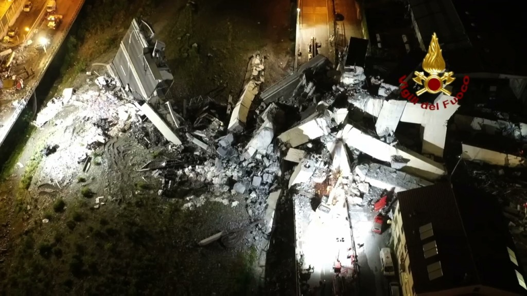 In this frame taken from a video released by the Italian firefighters, rescue teams work among the rubble of the collapsed Morandi highway bridge in G...