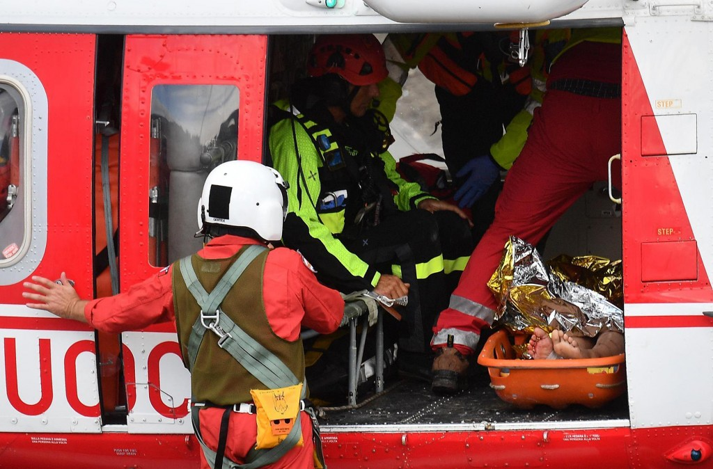 Firefighters load an injured person on a helicopter after the Morandi highway bridge collapsed in Genoa, northern Italy, Tuesday, Aug. 14, 2018. The h...