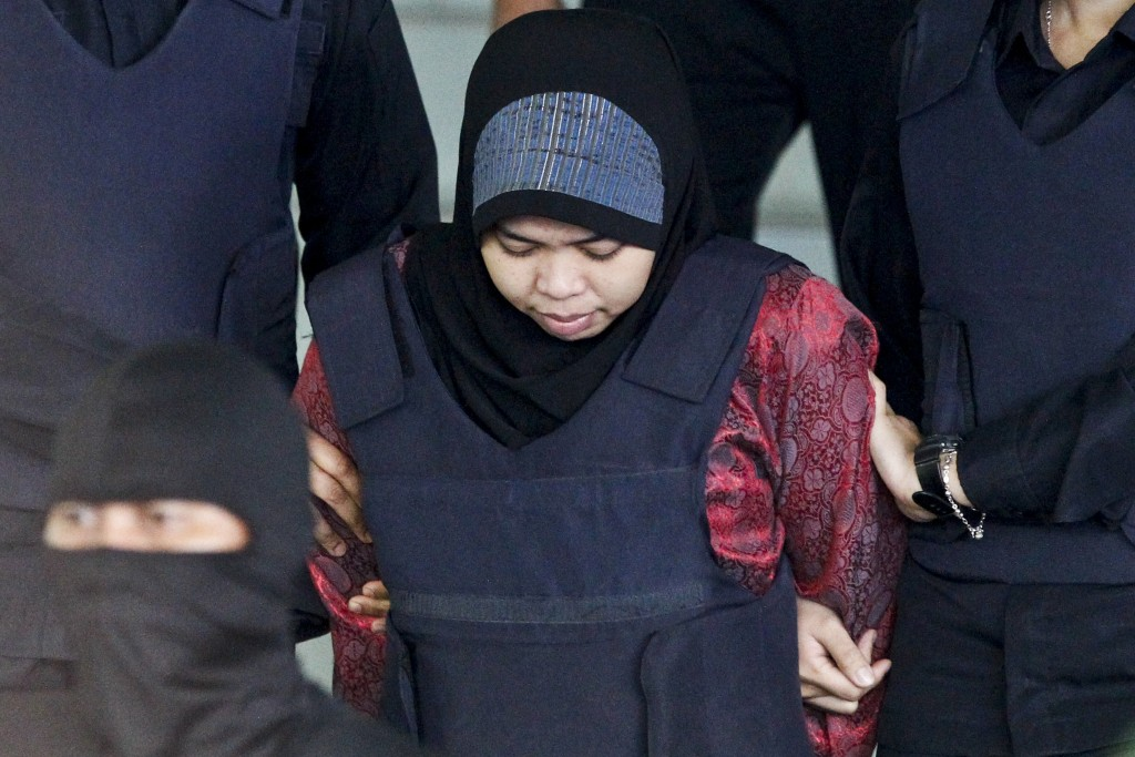 FILE - In this March 22, 2018, file photo, Indonesian Siti Aisyah is escorted by police as she leaves after a court hearing at Shah Alam High Court in