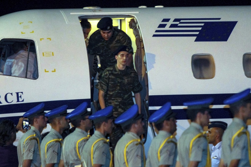Greek soldiers Aggelos Mitretodis, front, and Dimitros Kouklatzis, arrive at the airport of the northern city of Thessaloniki, after spending months i...