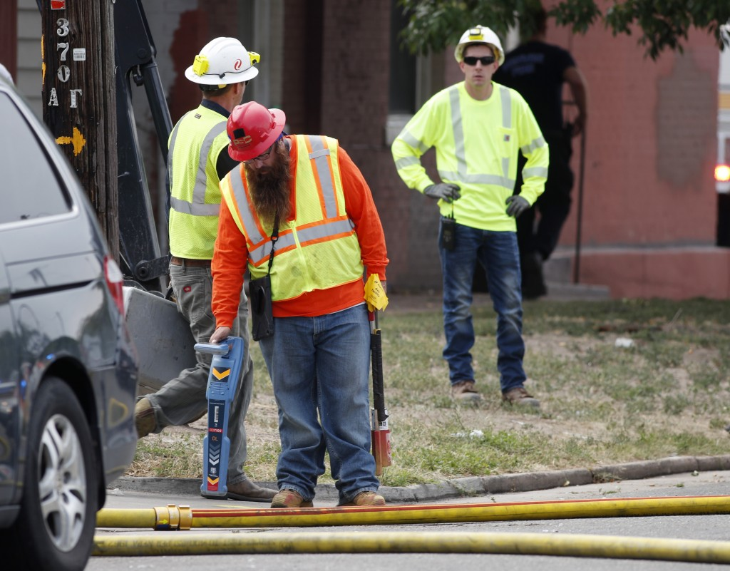 A worker checks for a natural gas leak near the scene of an apparent gas explosion in a row of homes along a block Tuesday, Aug. 14, 2018, in Denver. ...