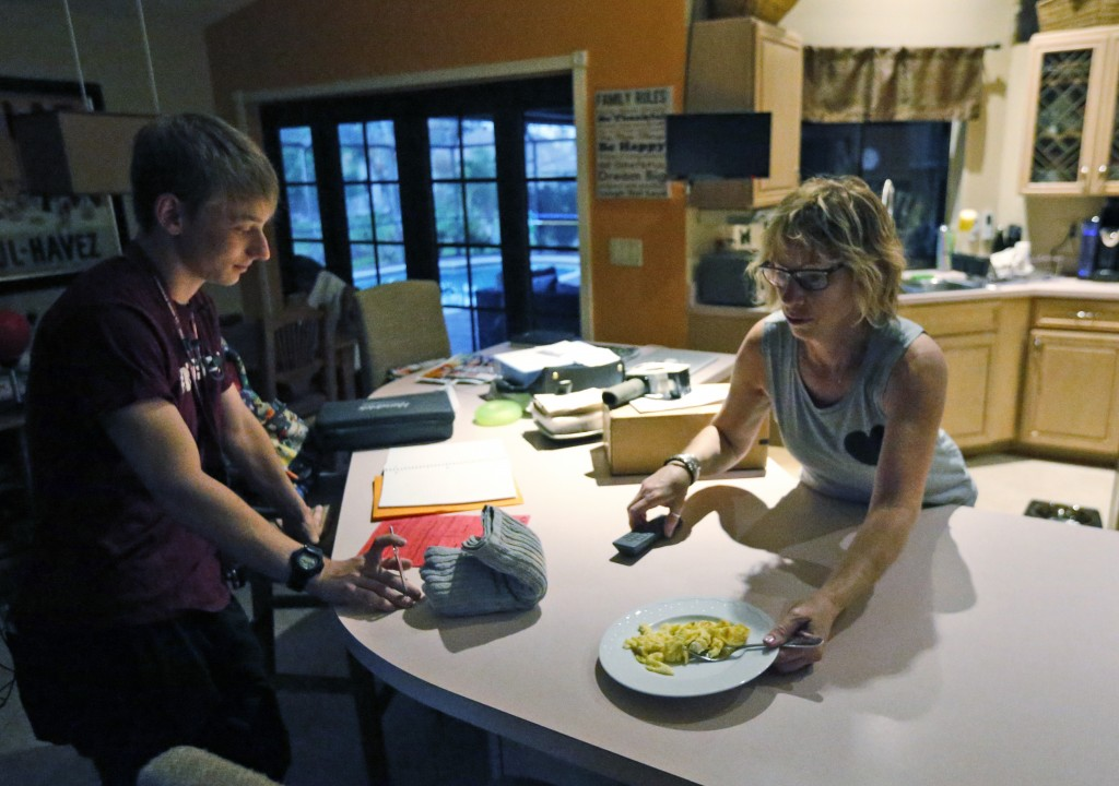 Amy Shebes, right, makes her son Charlie , 16, a junior at Marjory Stoneman Douglas High School, breakfast, as he prepares to go to school, Wednesday,...
