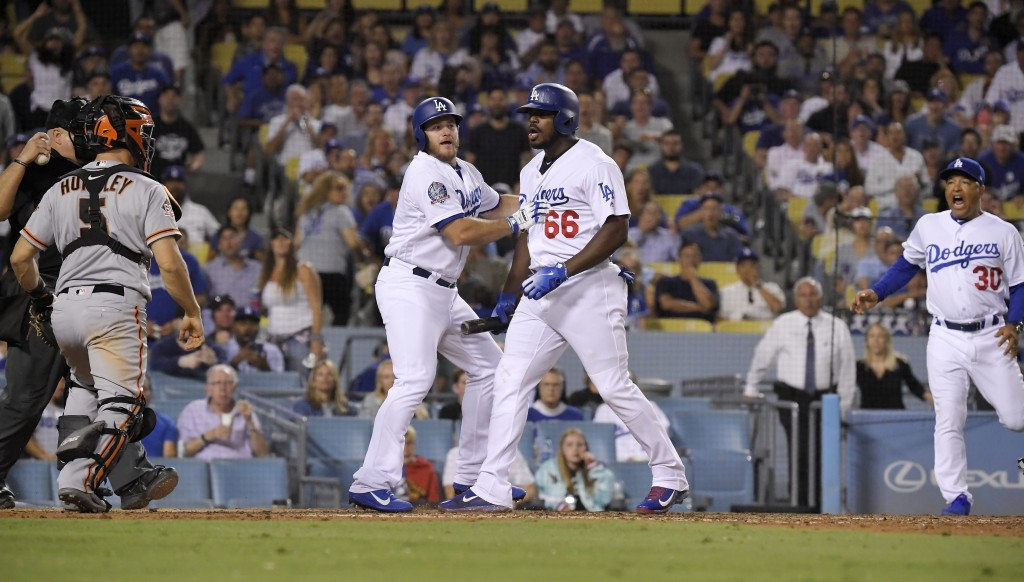 San Francisco Giants catcher Nick Hundley, second from left, and Los Angeles Dodgers' Yasiel Puig, second from right, argue as Max Muncy, center, hold...