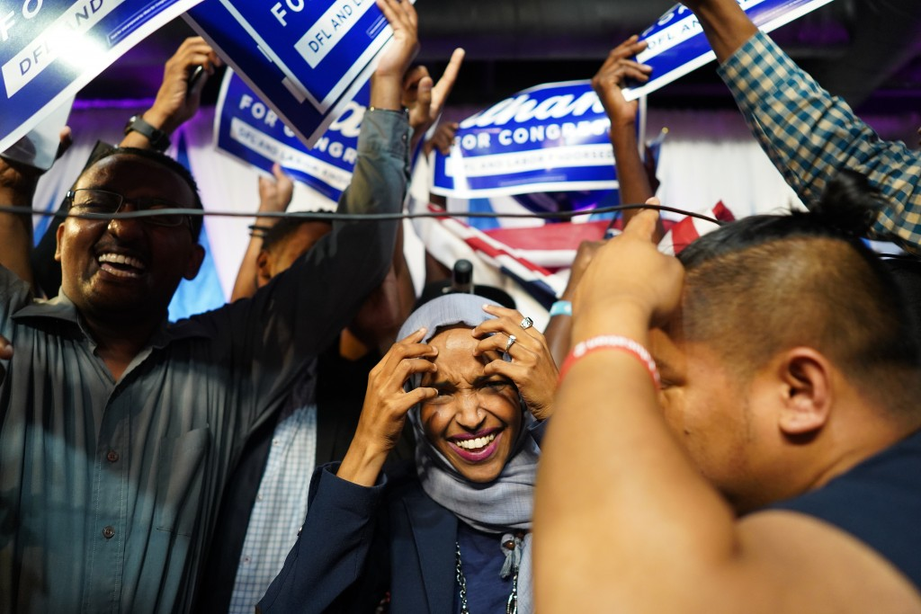 Minnesota Rep. Ilhan Omar, center, celebrates with her supporters after her Congressional 5th District primary victory, Tuesday, Aug. 14, 2018, in Min...