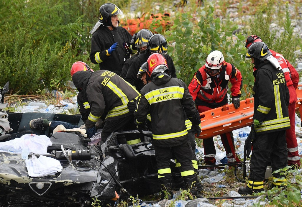 EDS NOTE, GRAPHIC CONTENT -- Firefighters recover from a car the body of a victim of the Morandi highway bridge collapse, in Genoa, northern Italy, Tu...