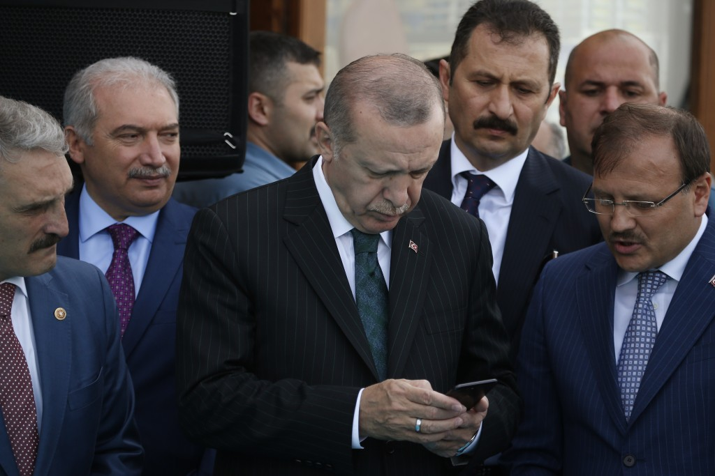 FILE - In this Friday, May 4, 2018 file photo, Turkey's President Recep Tayyip Erdogan, center, looks at his phone during a ceremony in Istanbul. Erdo...
