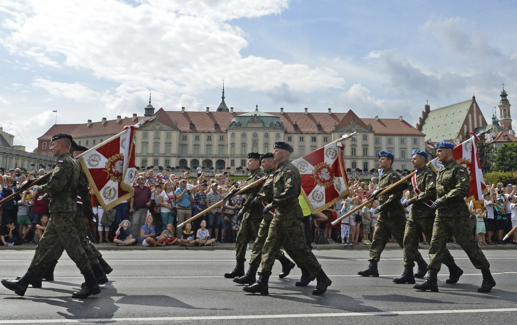 Polish Army soldiers holding military unit banners march on one of the city's main streets during a yearly military parade celebrating the Polish Army...
