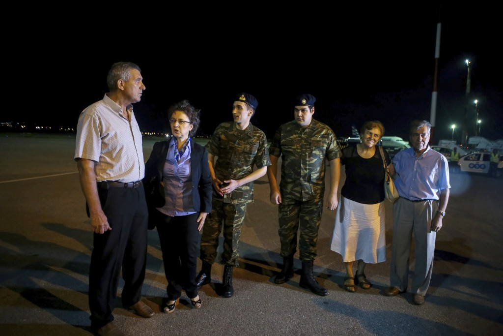 Greek soldiers Aggelos Mitretodis, third left, and Dimitros Kouklatzis, third right are welcomed by their parents during their arrival at the airport ...