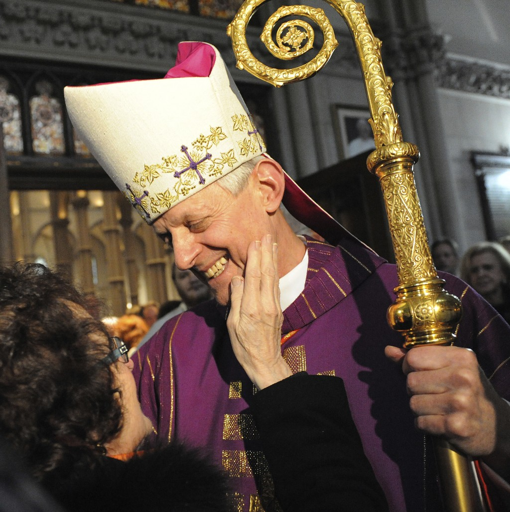 In this Dec. 12, 2010, photo, Cardinal Donald Wuerl, the Archbishop of Washington, greets a woman after giving a Mass of Thanksgiving at St. Paul Cath...