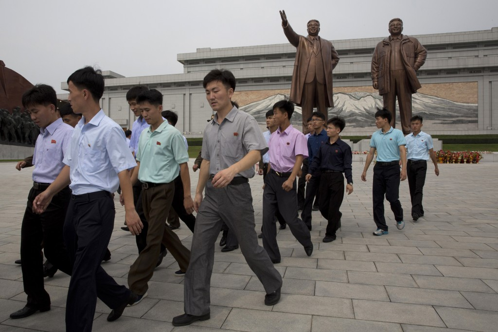 Men leave after paying their respects before the giant bronze statues of late North Korean leaders Kim Il Sung and his son Kim Jong Il during the anni...