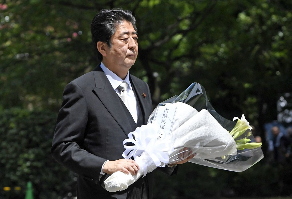 Japanese Prime Minister Shinzo Abe carries a bouquet of flowers at the Chidorigafuchi National Cemetery for unidentified remains of the nation's war d...